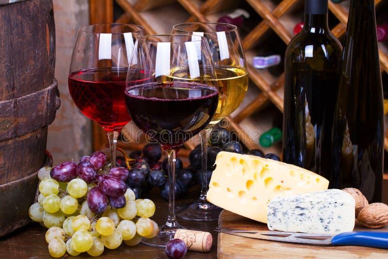 Rosso, vetri rosa e bianchi e bottiglie di vino Uva, dadi, formaggio e vecchio barilotto di legno immagini stock