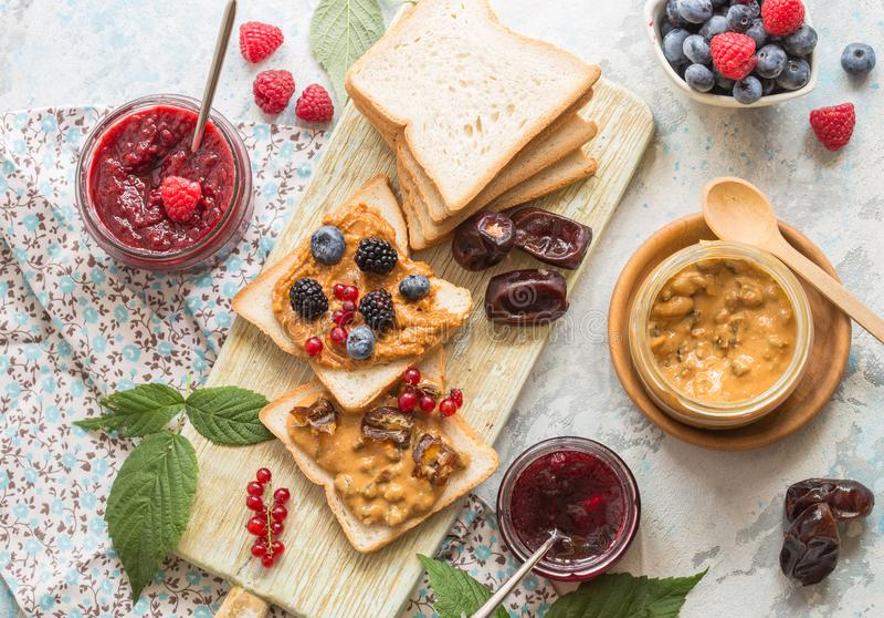 Rosta bröd med hemlagat jordgubbedriftstopp och jordnötsmör som tjänas som med bäret Top beskådar royaltyfri foto