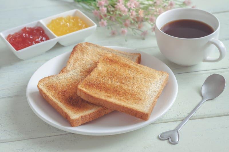 Rosta bröd på plattan med driftstopp- och kaffekoppen royaltyfri bild