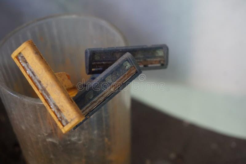 Rosta den gula och svarta använda plast- rakapparatrakkniven arkivbild
