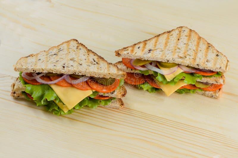 Rosta grillade ostbacon, grönsallat och tomatsmörgåsar arkivbilder