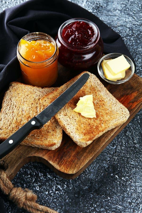 Rosta på bröd med hemlagat jordgubbedriftstopp och orange marmelad fotografering för bildbyråer
