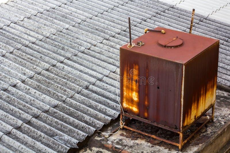 Rosta vattenlagringsbehållaren på taket av huset royaltyfria bilder