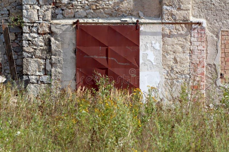 Rostad metall som glider lagerdörrar som framme monteras på den gamla förfallna väggen med högväxt gräs och små blommor på överge arkivfoton