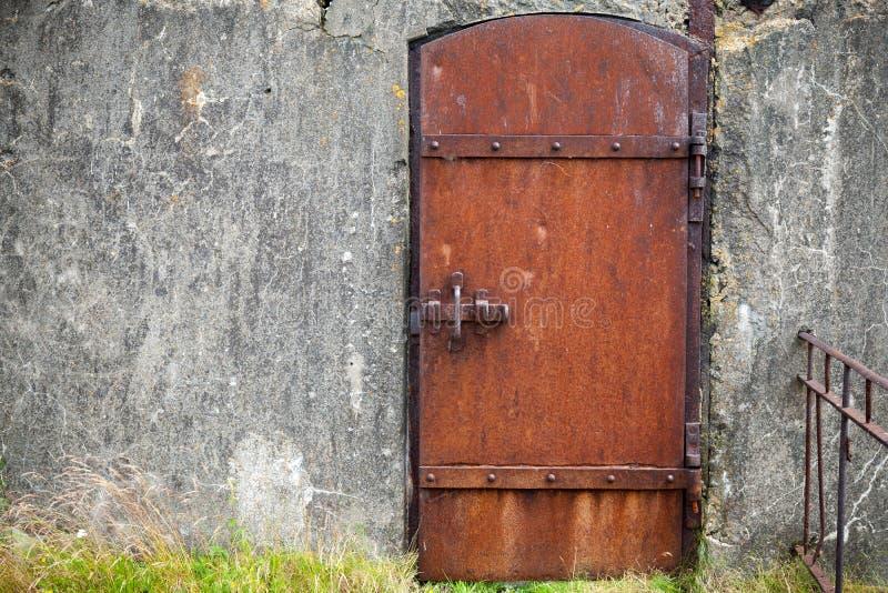 Rostad metalldörr i den gamla väggen, bakgrundstextur royaltyfri bild