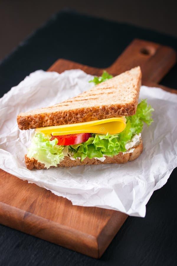 Rostad smörgås med salladsidor, tomater och ost med gaffeln på en skärbräda på en mörk bakgrund arkivfoton
