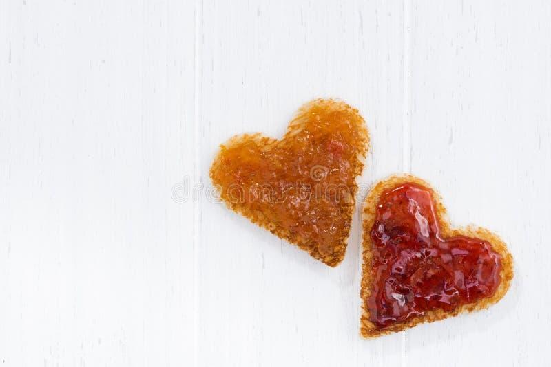 rostade bröd i hjärtaform med frukt sitter fast på vit träbakgrund arkivbild