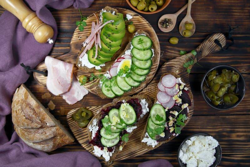 Rostade bröd med avokadon, beta och skinka royaltyfria bilder