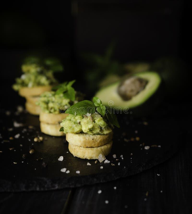 Rostade bröd med pasta från avakado eller guacamole och kryddor på trätabellen med frukter, selektiv fokus, begrepp royaltyfri bild