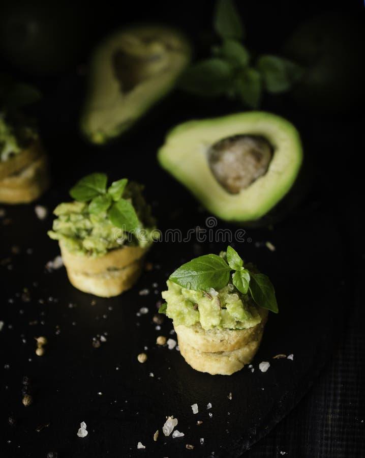 Rostade bröd med pasta från avakado eller guacamole och kryddor på trätabellen med frukter, selektiv fokus, begrepp arkivbilder
