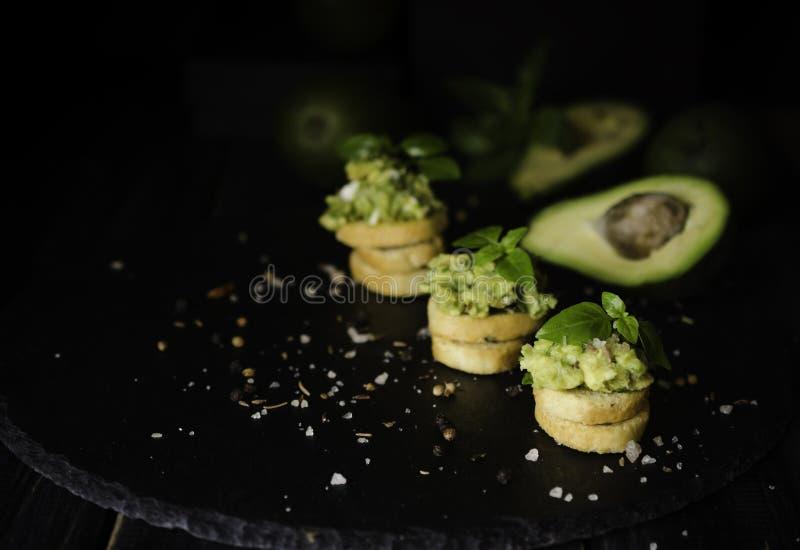 Rostade bröd med pasta från avakado eller guacamole och kryddor på trätabellen med frukter, selektiv fokus, begrepp royaltyfri fotografi