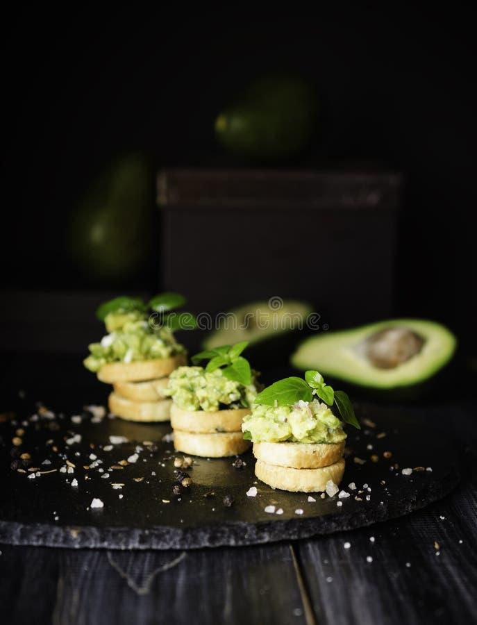 Rostade bröd med pasta från avakado eller guacamole och kryddor på trätabellen med frukter, selektiv fokus, begrepp fotografering för bildbyråer
