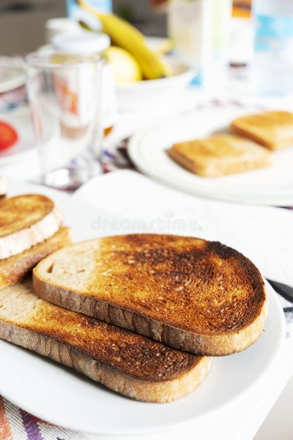 Rostade bröd på en tabell ställde in för frukost eller matställe arkivfoto