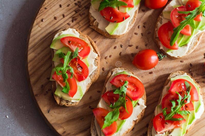 Rostade br?d med avokadot och tomater royaltyfri foto