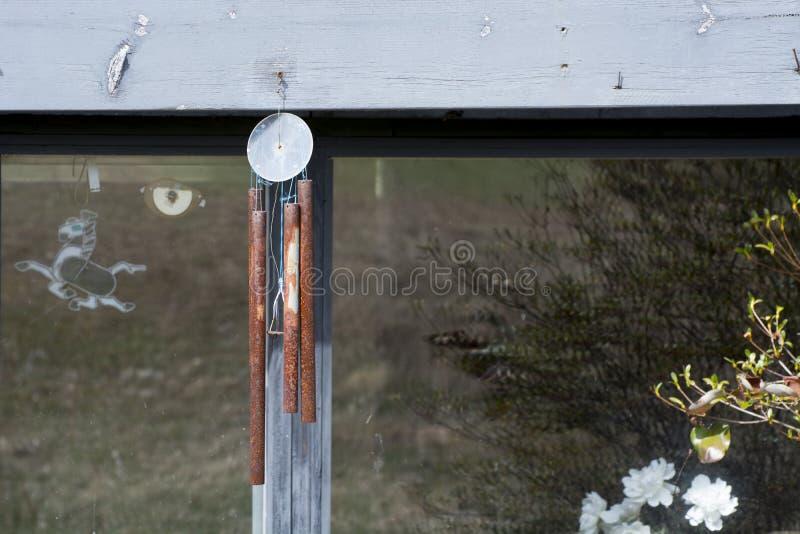 Rostade chimes med fönsterbakgrund arkivbilder