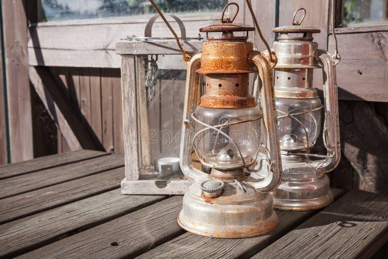 Rostade fotogenlampor står på den gamla trätabellen arkivbild