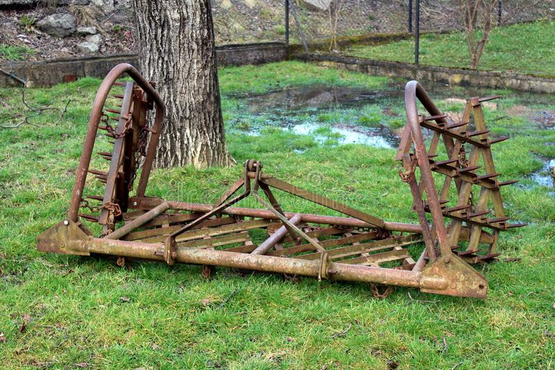 Rostade gamla harv på grönt gräs fotografering för bildbyråer