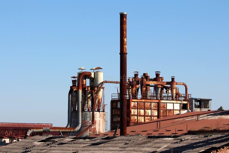 Rostade metalllampglas som överst omges med stora lagringssilor av förstörda tak på det övergav industriella komplexet royaltyfri bild