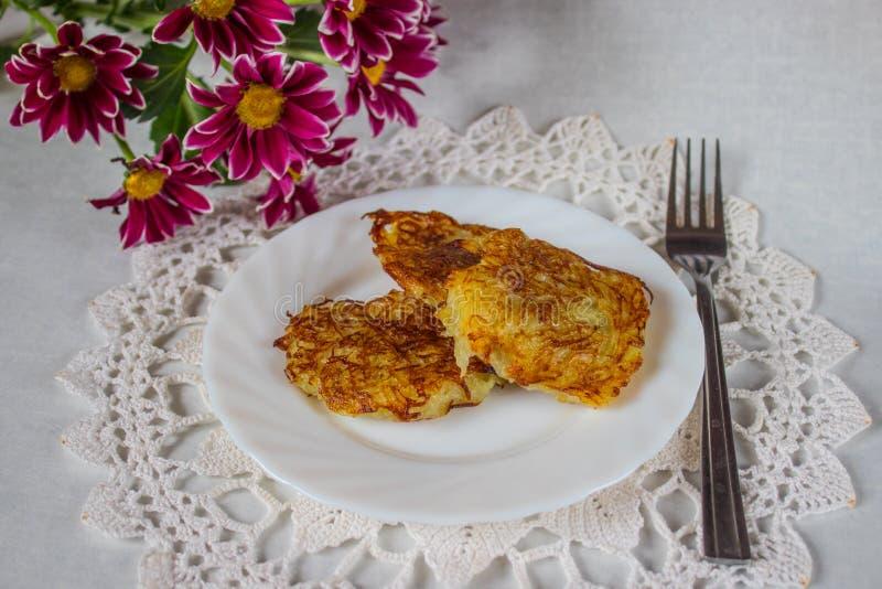 Rostade raggmunkar på en platta med blommor och en servett royaltyfri foto