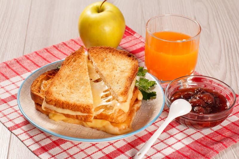 Rostade skivor av bröd med ost, exponeringsglas av orange fruktsaft, citronen, oliv, äpplet och bunken med jordgubbedriftstopp på arkivfoton