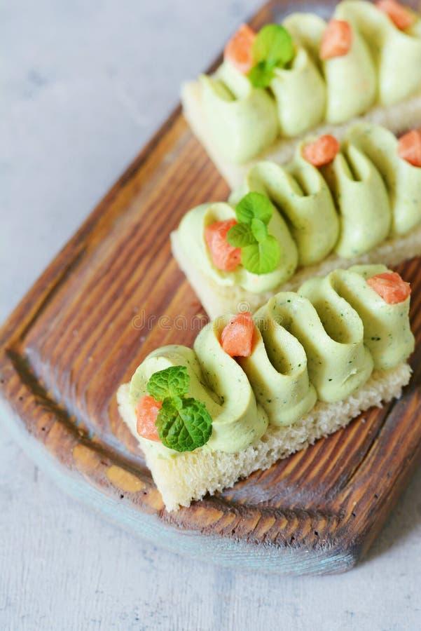 Rostat bröd med avokadomousse och gräddost med laxservice med den limefruktfruktsaft och mintkaramellen royaltyfri foto
