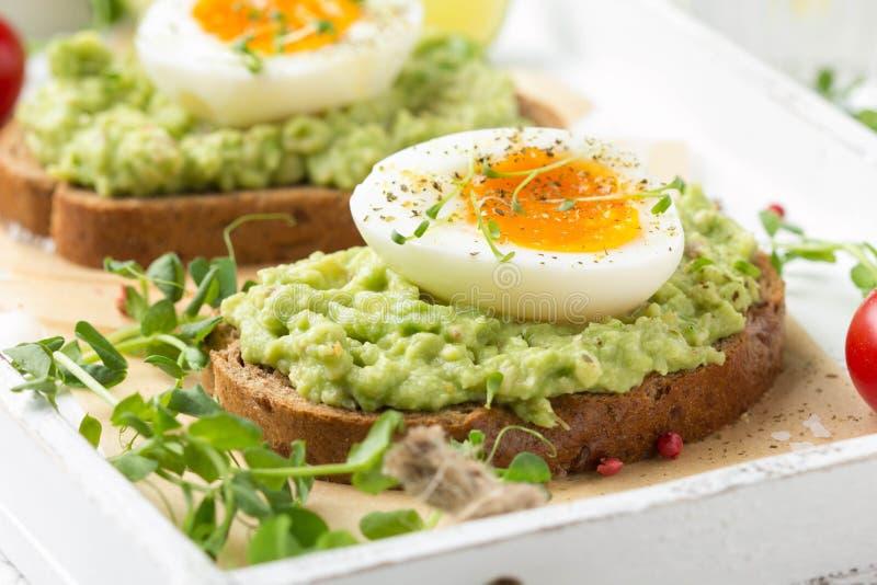 Rostat bröd med avokadopuré och det löskokta ägget på det vita magasinet, vätskeäggula, läcker frukost, ljus smörgås sund mat royaltyfri bild