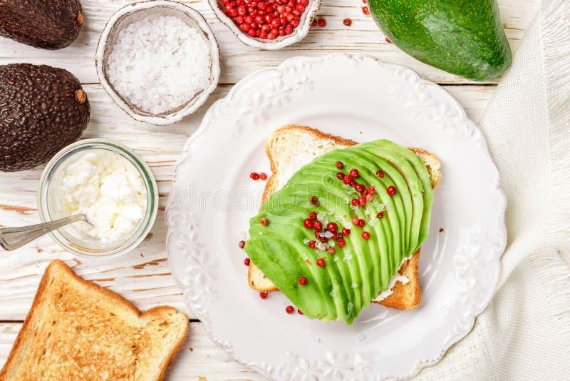 Rostat bröd med avokadot, kesoricotta, det grova havet saltar och rosa peppar royaltyfria bilder