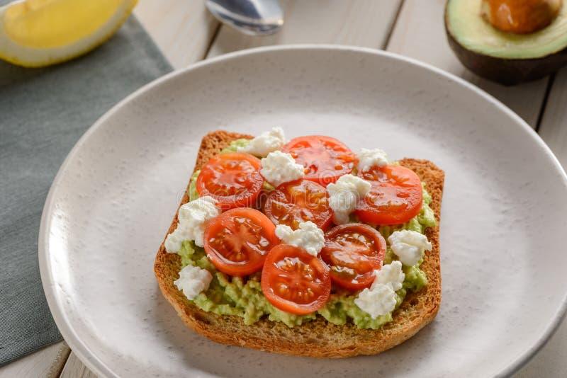 Rostat bröd med avokadot, ricotta, tomat royaltyfri foto