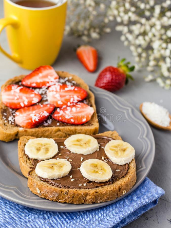 Rostat br?d med choklad och frukter p? en gr? platta Jordgubbar och bananer p? stenk?ksbordbakgrund Top besk?dar royaltyfria bilder