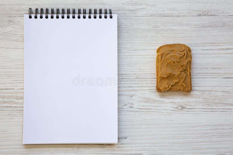 Rostat bröd med den jordnötsmör och notepaden över den vita trätabellen, bästa sikt arkivfoton