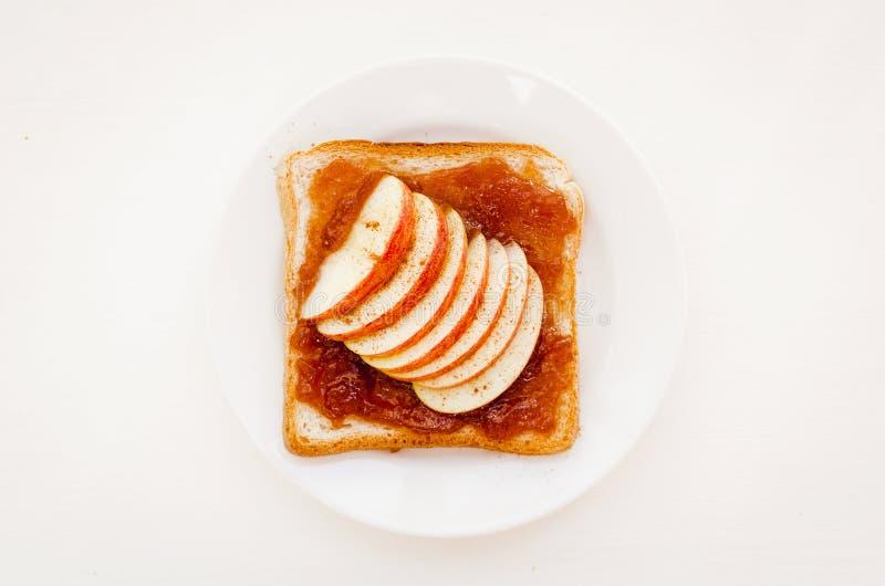 Rostat bröd med ett äppledriftstopp och skivor av nya äpplen på plattan på en vit tabell Bästa sikt för läcker söt frukost royaltyfria foton
