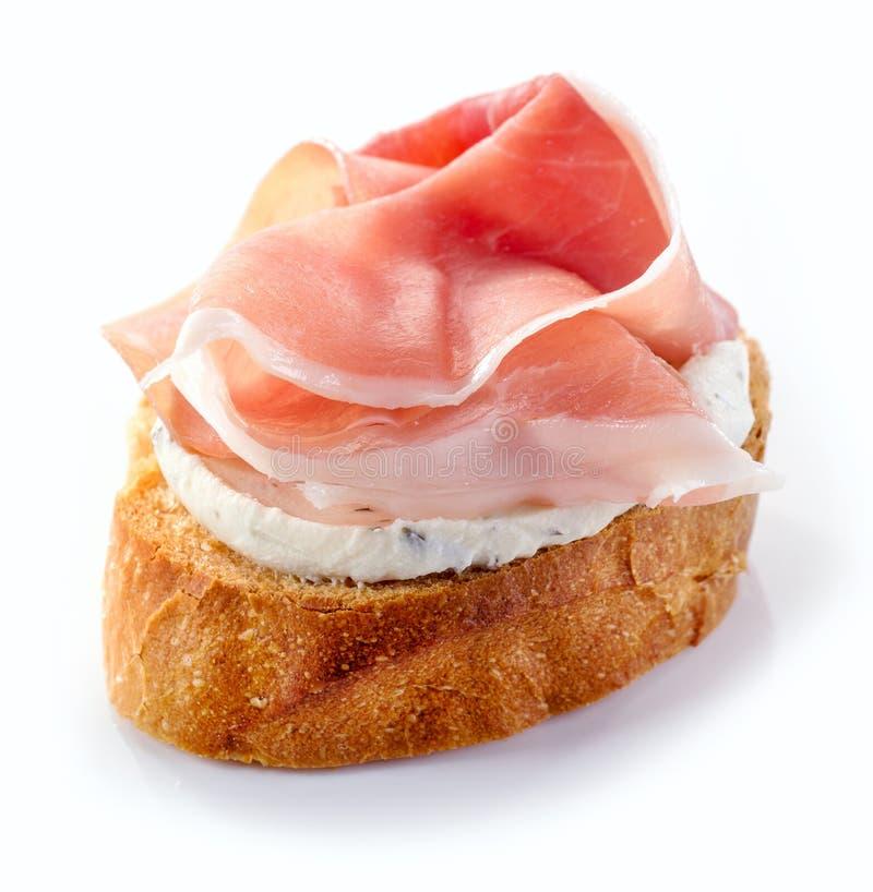 Rostat bröd med gräddost och prosciuttoen arkivfoto