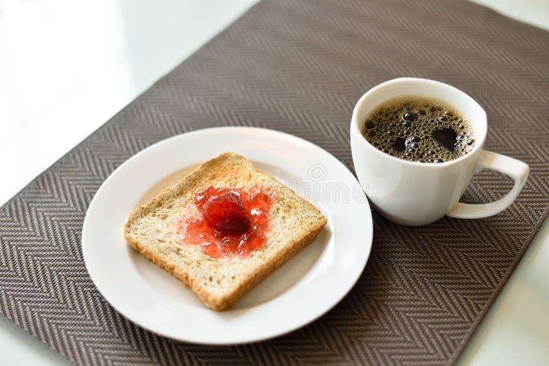 Rostat bröd med jordgubbedriftstopp och varmt svart kaffe royaltyfria bilder