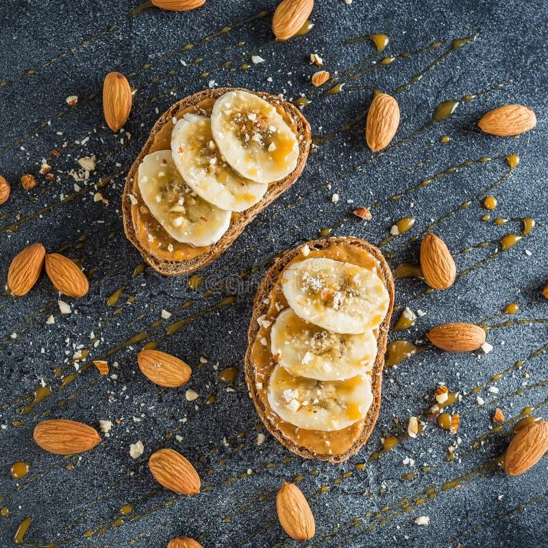 Rostat bröd med jordnötsmör, bananen och mandelmuttrar Banta naturliga den lekmanna- frukostlägenheten, bästa sikt arkivfoton