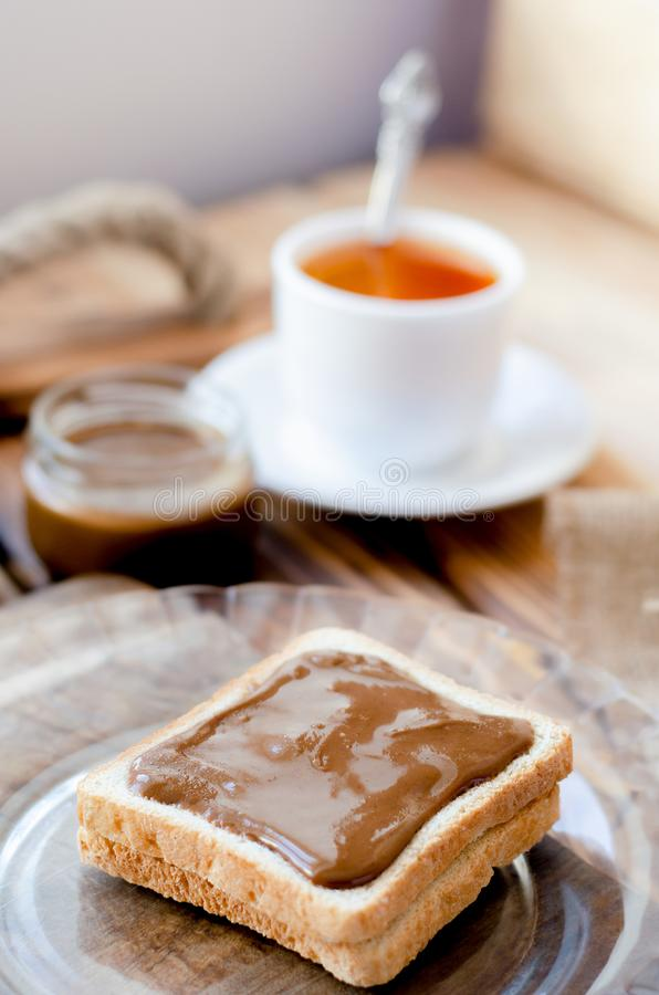 Rostat bröd med jordnötsmör och en kopp te arkivfoto