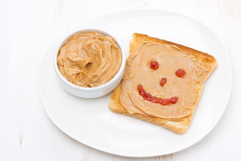 Rostat bröd med jordnötsmör och ett målat leende på en platta fotografering för bildbyråer