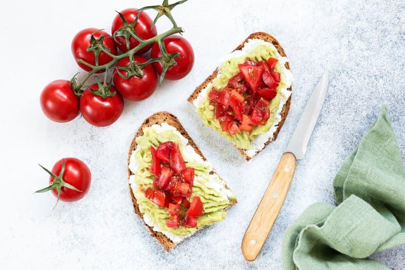 Rostat bröd med ost, avokadot och tomaten royaltyfri foto