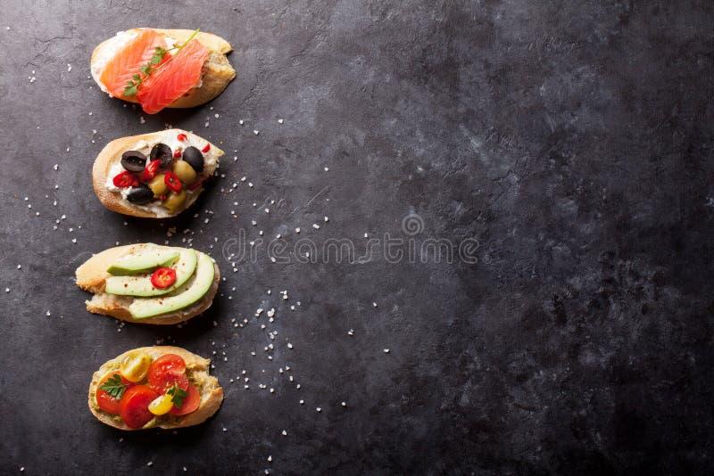 Rostat bröd skjuter in med avokadot, tomater, lax royaltyfria bilder