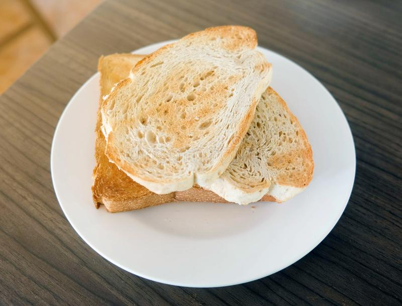 Rostat brödbröd för två skivor i den vita plattan på trätabellen royaltyfri bild