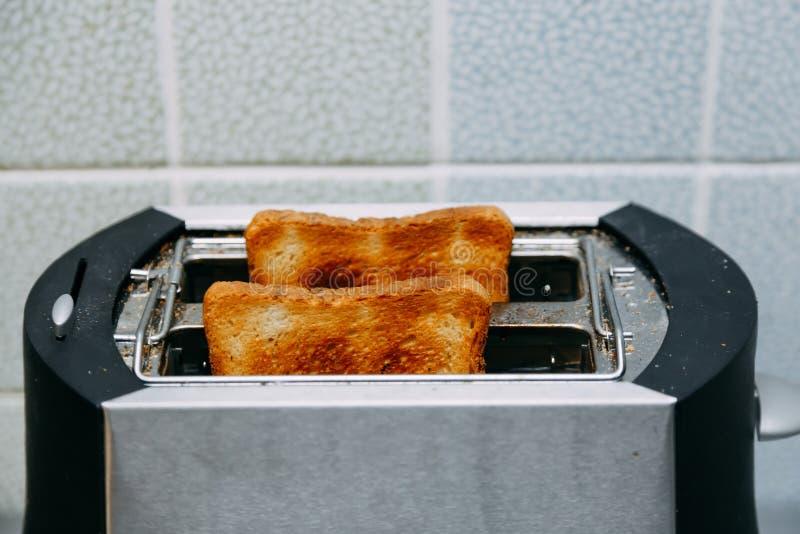 Rostat br?d i en br?drost Brödrost med smakliga frukostrostade bröd på tabellen arkivfoton