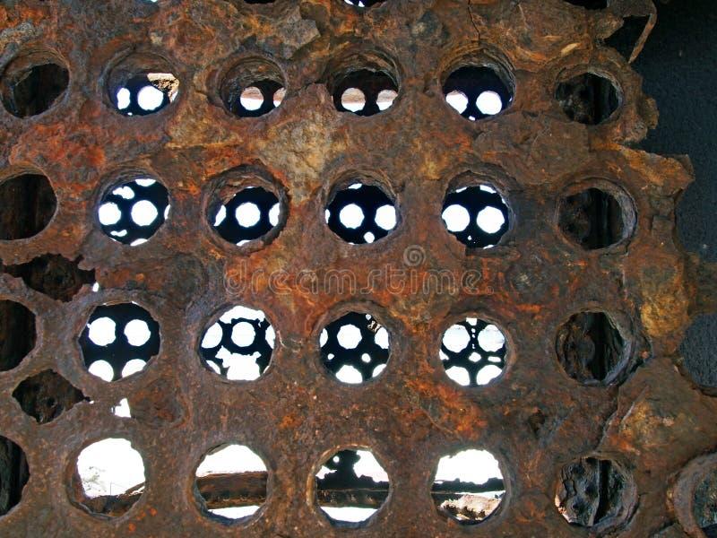 Rostat förfalla järnpaneler som täckas i runda hål med ljus som ändå skiner på föråldrat tungt maskineri royaltyfria bilder
