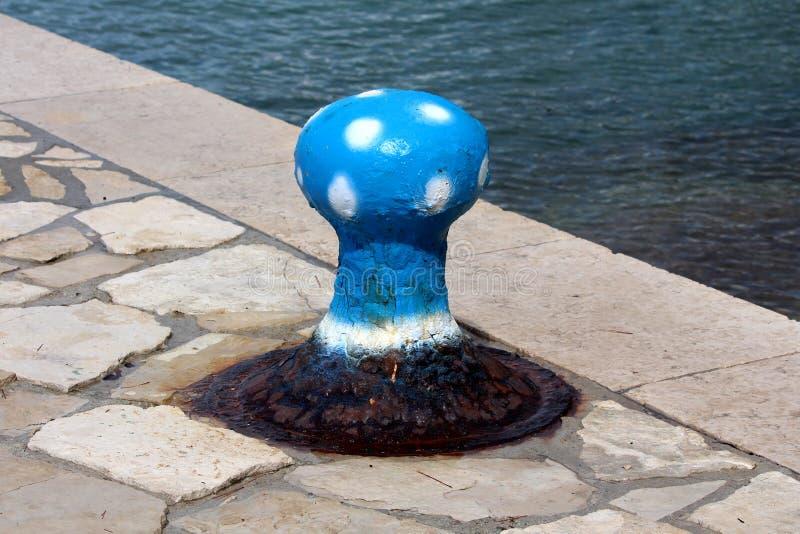 Rostat gammalt järn som förtöjer pollaren som formas och målas som den blåa champinjonen med vita fläckar som monteras på den tra arkivbilder