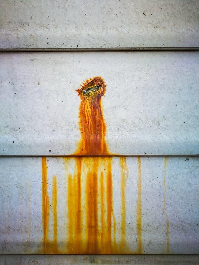 Rostfläck häller på cementväggen med rostig metall inom royaltyfri fotografi