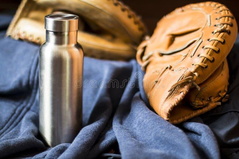 Rostfreie Isolierflasche mit Baseball und Handschuh stockfoto