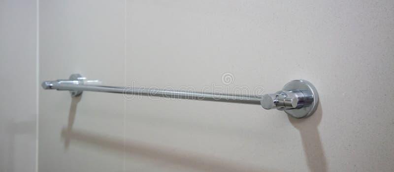 Rostfreies silbernes Tuch Schienen auf grauer Fliesenwand stockfotografie