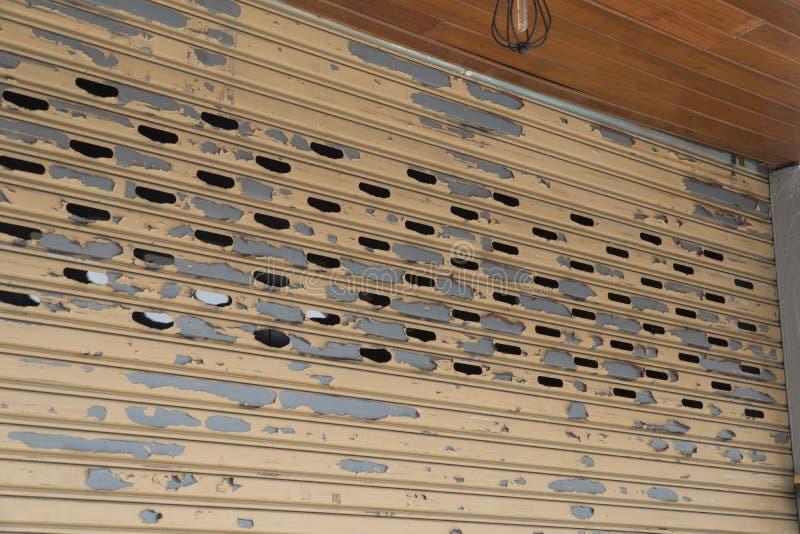Rostfri dörrbakgrund för rullande slutare, gammal glidbanadörr, rullslutaretextur arkivbild