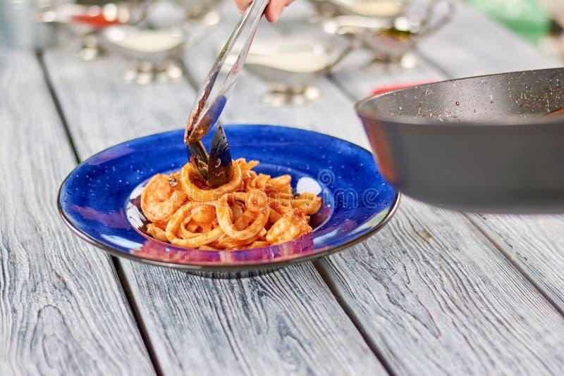 Rostfri tång för kök som sätter musslan på pasta royaltyfri fotografi