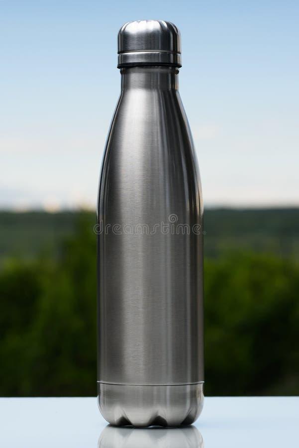 Rostfri termos, vattenflaska på himlen och skogbakgrund Vertikalt foto royaltyfria foton