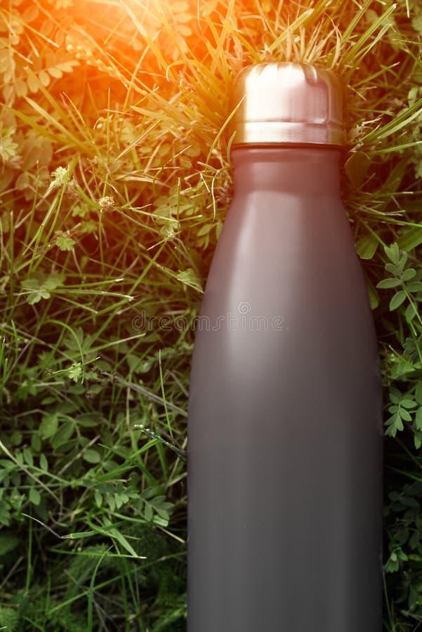 Rostfri termosflaska för vatten, svart färg på bakgrund för grönt gräs med solljuseffekt fotografering för bildbyråer