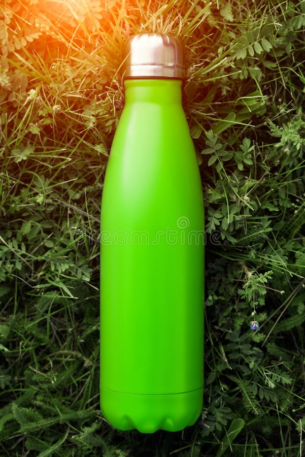 Rostfri termosvattenflaska, ljus - grön färg Modell på bakgrund för grönt gräs med solljuseffekt fotografering för bildbyråer
